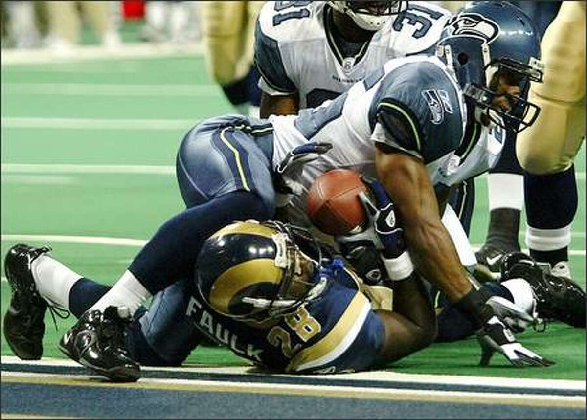 Marshall Faulk scores his first touchdown on a 6-yard pass from Marc Bulger, despite the efforts of Seahawks strong safety Reggie Tongue. Faulk, who ran for 183 yards, caught seven passes for 52.