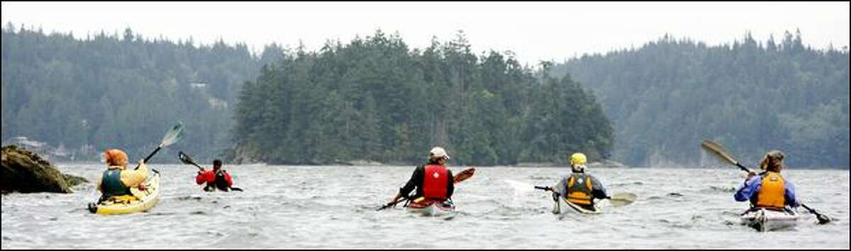 A group of kayakers set a heading for Chuckanut Island, a 5-acre preserve in Chuckanut Bay owned by The Nature Conservancy. The uninhabited island has no facilities and is open to day use only.