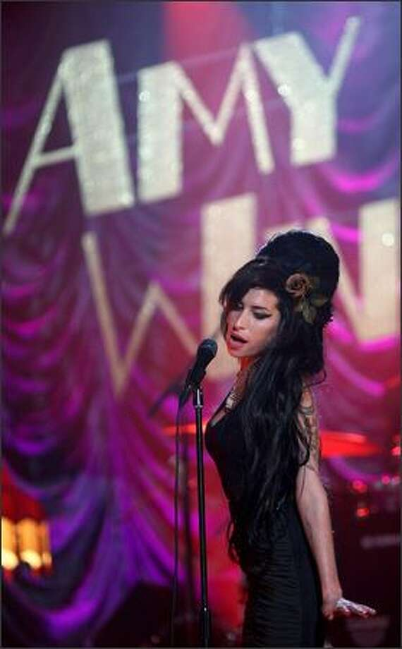 Amy Winehouse performs for the Grammy Awards via video link. Winehouse won five awards from her 6 nominations -- record of the year, best new artist, song of the year, pop vocal album and female pop vocal performance. Photo: Getty Images