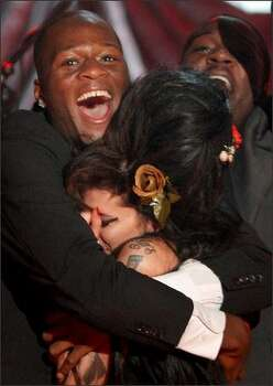 Amy Winehouse is hugged by band member Zalon. Photo: Getty Images