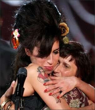 Amy Winehouse hugs her mother Janis after accepting a Grammy Award at The Riverside Studios in London. Photo: Getty Images