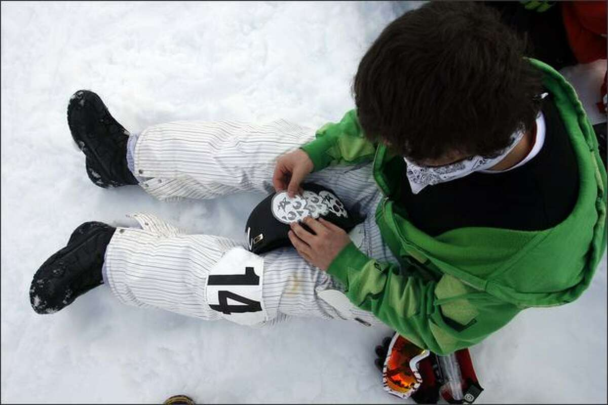 Nick Tochia, 15, from Carnation, places skull stickers on his helmet as he prepares for the competition.