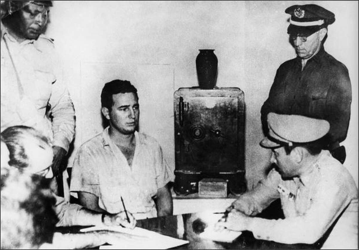 Fidel Castro, second from left, under arrest, after the July 1953 Moncada Barracks Attack. In this photo, he gives a deposition to Col. Alberto Del Río Chaviano, military chief of the Moncada Garrison, Maj. Jose Izquierdo, chief of police, and members of the Regimental Intelligence Service of Santiago de Cuba, at the Vivac in Santiago de Cuba, July 1953. AFP/Getty Images