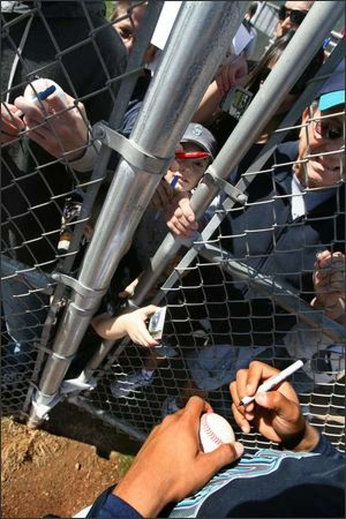 Fans press up against the fence as they try to get Felix Hernandez's autograph during the Seattle Mariners workout on the second day of full-squad worksouts in Peoria, Ariz.
