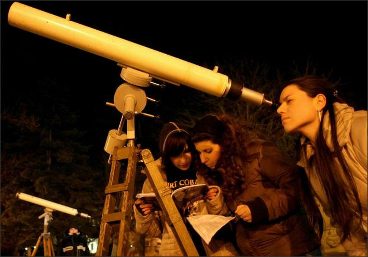 Amateur astronomers look at a partially eclipsed moon in the town of Varna, east of the Bulgarian capital Sofia. The last total lunar eclipse until 2010 occurred Wednesday night, with cameo appearances by Saturn and the bright star Regulus on either side of the veiled full moon. AP Photo/Petko Momchilov