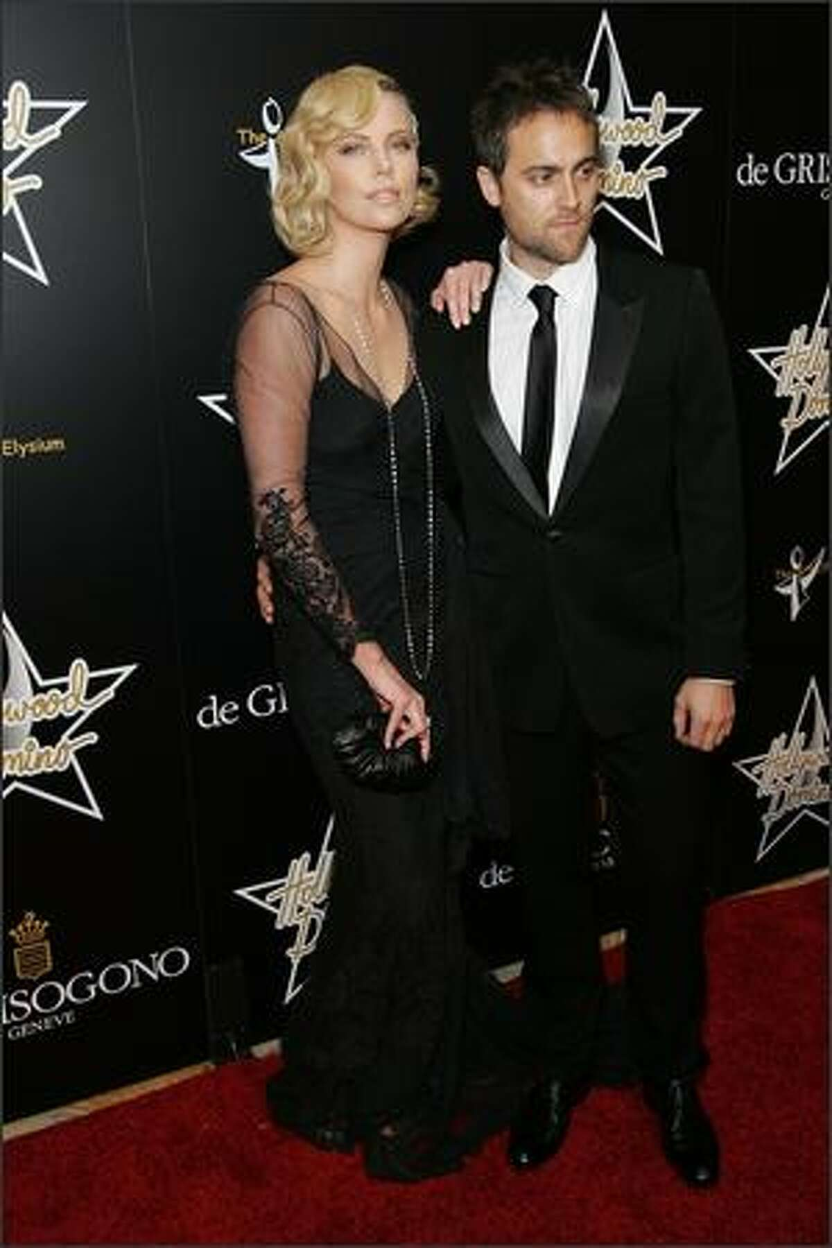Actress Charlize Theron and actor Stuart Townsend attend the 1st Hollywood Domino Tournament hosted by De Grisogono at the Beverly Hills Hotel in Beverly Hills, California.