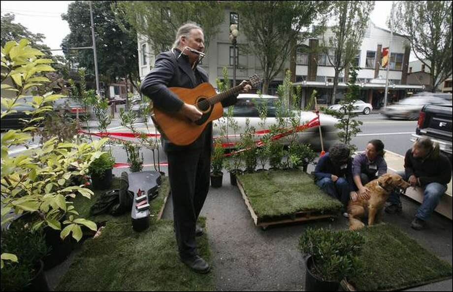 Singer-songwriter John Shaw headlined Friday's lunch hour in Columbia City at one of 31 sites around the city where parking spaces were converted to temporary, tiny parks. Photo: Paul Joseph Brown/Seattle Post-Intelligencer