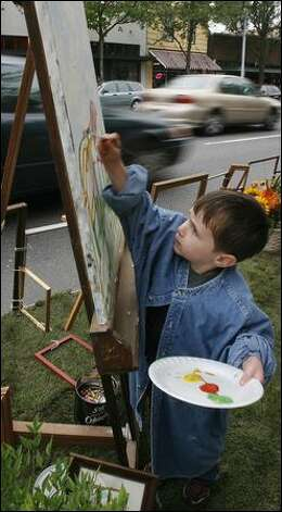Coling Pfister, 4, takes his turn painting at an easel set up in a parking space along Rainier Avenue South on Friday. Photo: Paul Joseph Brown/Seattle Post-Intelligencer