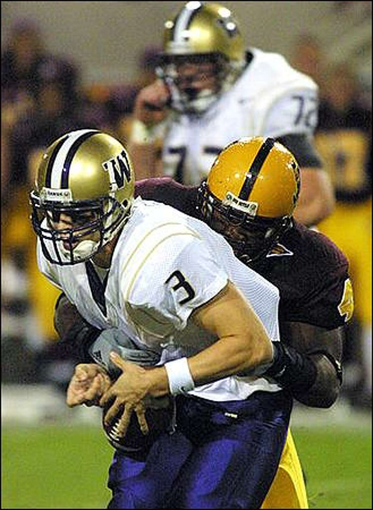 Arizona State defensive end Terrell Suggs, middle, sacks Washington quarterback Cody Pickett (3) as center Todd Bachert, top, looks on, during the first quarter, Saturday, Oct. 26, 2002, in Tempe, Ariz.(AP Photo/Roy Dabner)
