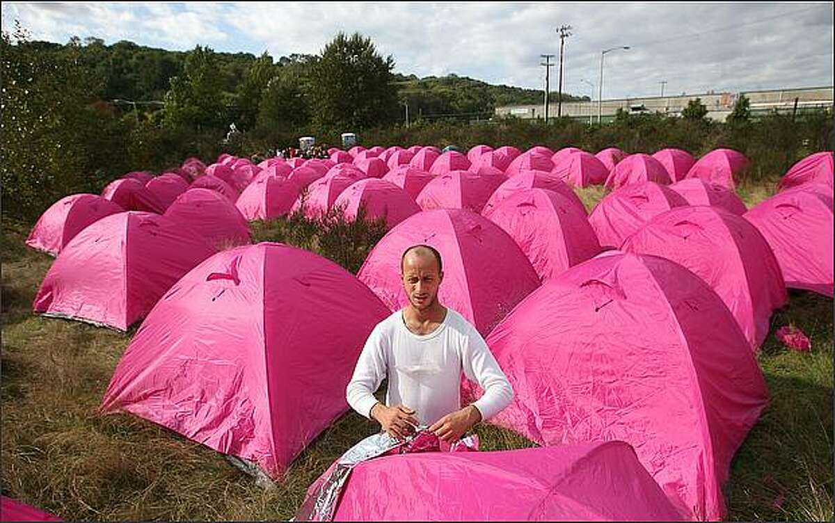 Advocates for the homeless set up about 150 fuchsia tents near the Duwamish River on Monday to draw attention to the needs of homeless people while taking a swipe at Seattle Mayor Greg Nickels. Randy, who has been homeless for seven years, works on putting a space blanket around his tent to help keep it warmer. Randy didn't want to give his last name.