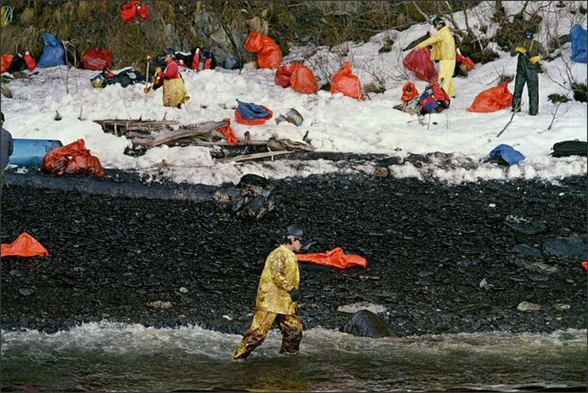 A cleanup worker walking through the oily surf at Naked Island on Prince Williams Sound, April 2, 1989, a week after the tanker Exxon Valdez oil tanker ran aground on March 24, 1989, and spilled 11 million gallons of crude oil.