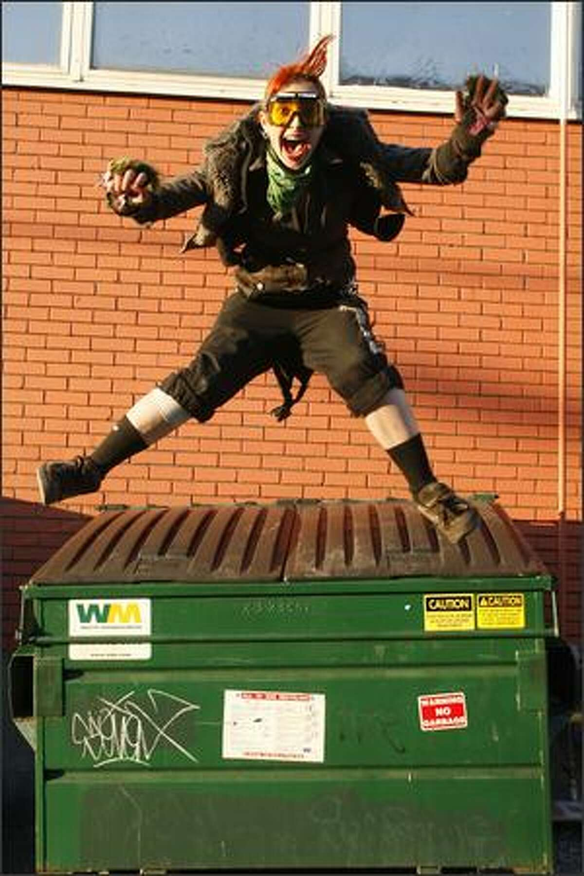 DUMPSTER JUMPSTER -- Alex Collins leaps from a dumpster near Capitol Hill.