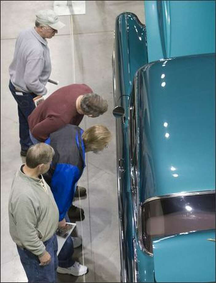 Visitors look at 1957 Chevy Bel Air Sedan owned by Ken and Angie Thomas The Seattle Roadster Show brought 283 cars, motorcycles and trucks to Qwest Field Event Center for a show of color, design, and shinny chrome for what looks like will be a gray rainy weekend. Photo: Grant M. Haller, Seattle Post-Intelligencer