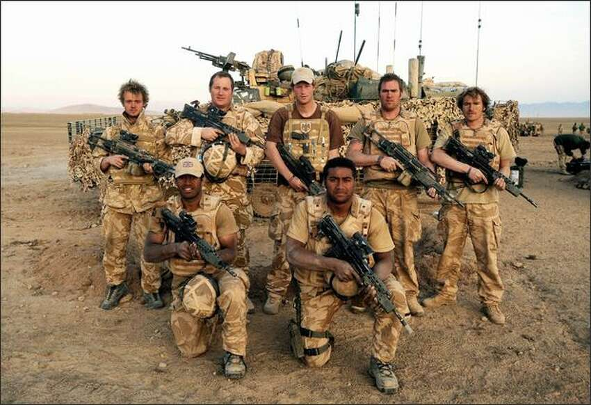 In this photo made available Sunday March 2, 2008, Britain's Prince Harry, center back, standing with other soldiers in his battle group as they pose for a photograph Feb.19, 2008, in the desert in Helmand province in Southern Afghanistan. Back row, from left, Lance Corporal Frankie O'Leary, Corporal of Horse Paul Carrington, Prince Harry, Lance Corporal of Horse Chris 'Dougie' Douglass, Lance Corporal Steve 'Geri' Halliwell. Front, drivers GV and Max. Prince Harry returned to Britain Saturday March 1, after news reports revealed details about his 10-week active military service in Afghanistan, and it was deemed too dangerous for him and other troops who would become a target if he remained.