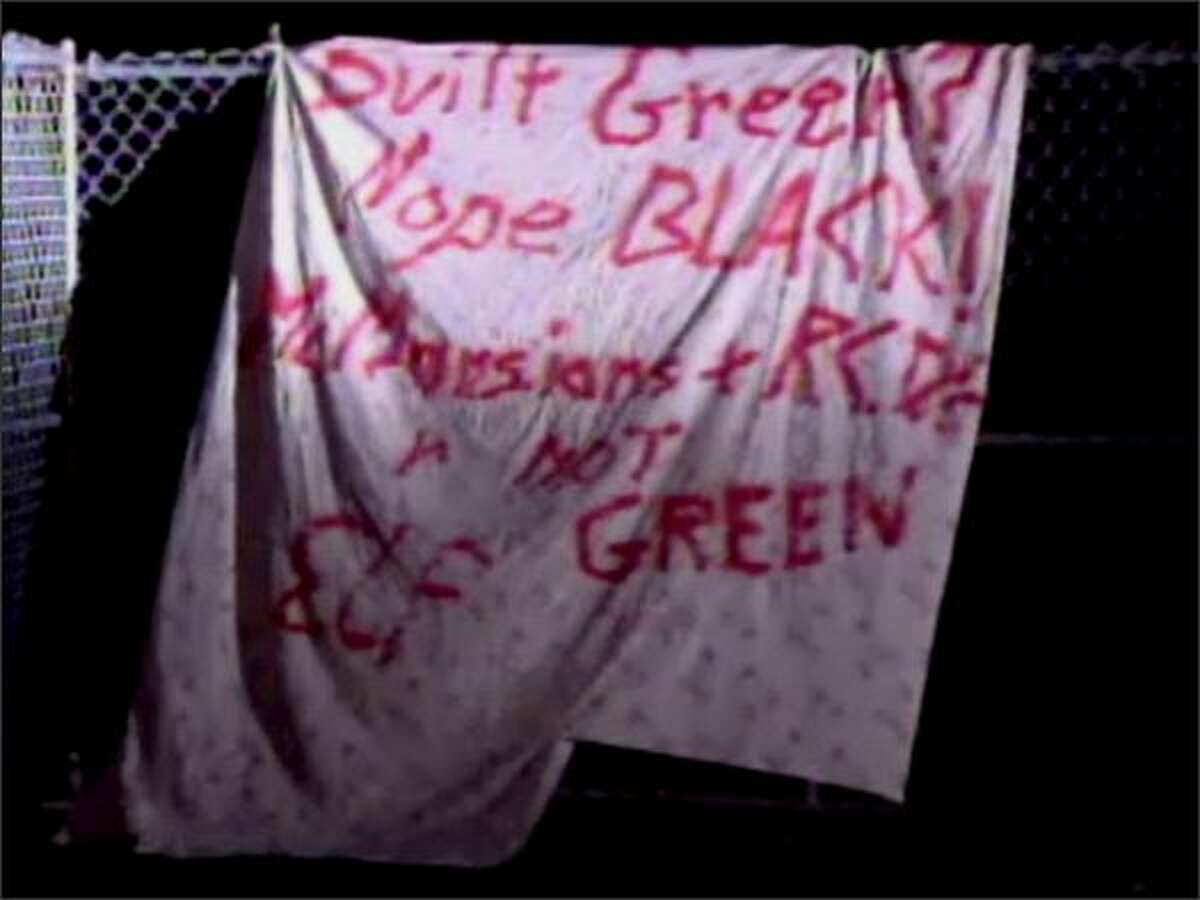 """A sign found near several luxury homes that burned Monday is shown. The sign reads, """"Built Green? Nope Black! McMansions and R.C.D.'s R not green. ELF."""" (AP Photo/KING TV 5)"""