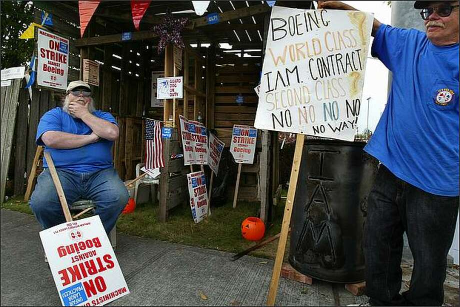 Terry Moore, left, a plant maintenance employee, and James Carey, a crane mechanic for Boeing for 35 years, picket outside a Boeing plant in Renton this week. Moore wants better medical coverage while Carey believes the company should keep the jobs in the U.S. and not outsource many of them internationally. Photo: Karen Ducey/Seattle Post-Intelligencer