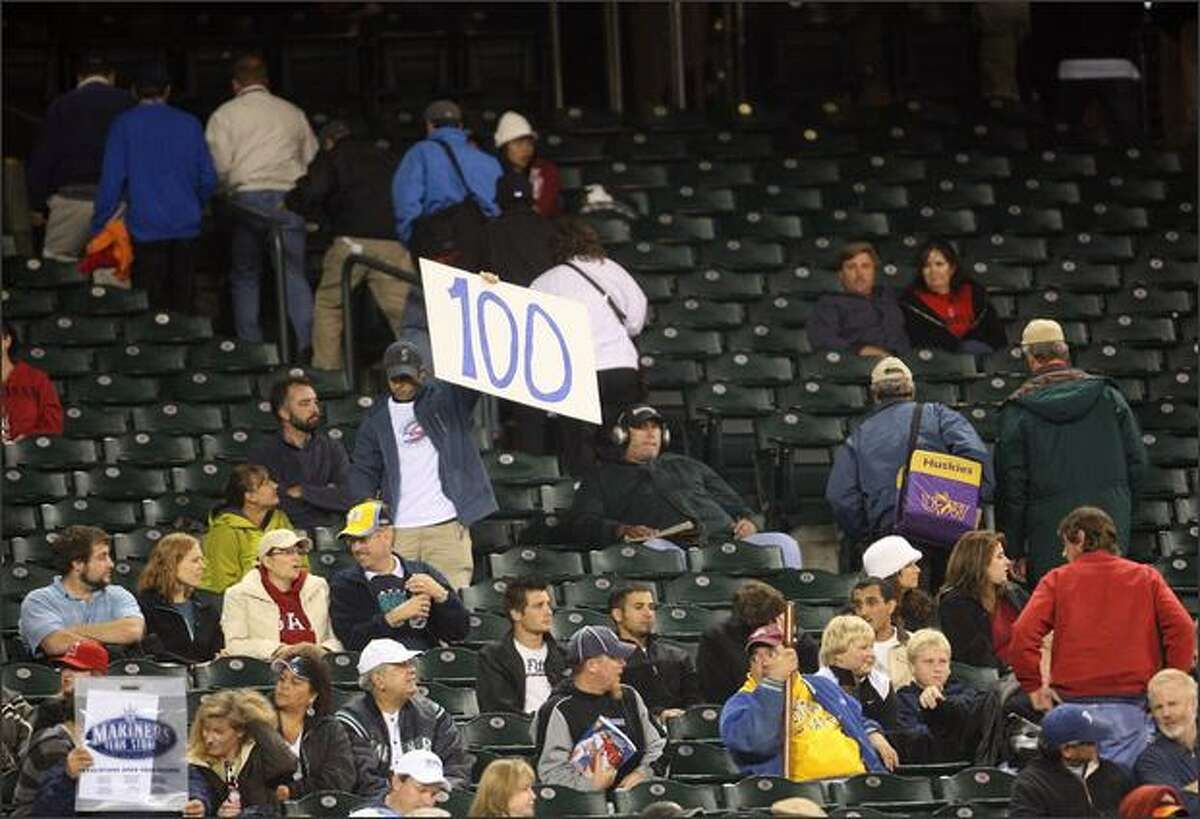 A fan hoists a sign to mark the occasion of the Mariners' 100th loss of the season.