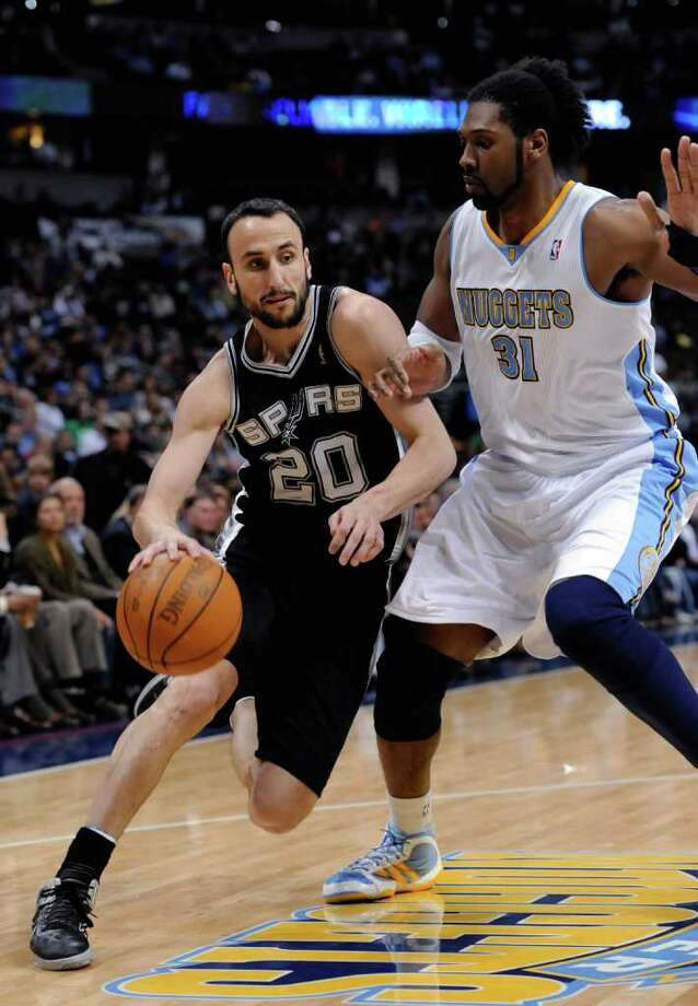 San Antonio Spurs guard Manu Ginobili (20), from Argentina, drives past Denver Nuggets center Nene (31), from Brazil, during the first quarter of an NBA basketball game Wednesday, March 23, 2011, in Denver. Photo: AP