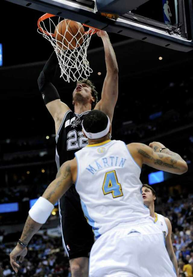 San Antonio Spurs forward Tiago Splitter (22), from Brazil, dunks over Denver Nuggets forward Kenyon Martin (4) during the first quarter of an NBA basketball game Wednesday, March 23, 2011, in Denver. Photo: AP