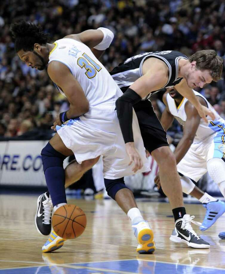 San Antonio Spurs forward Tiago Splitter, right, from Brazil, and Denver Nuggets center Nene (31), also from Brazil, scramble for a loose ball during the second quarter of an NBA basketball game Wednesday, March 23, 2011, in Denver. Photo: AP