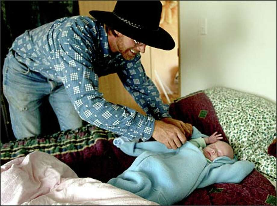 Chris Childers takes a break from his chores on a cattle farm near Winlock to check on his son, Nathaniel, 2 months old. Nathaniel bears a striking resemblance to Childers' son Brady, who died in 1997 after going into cardiac arrest. Photo: Meryl Schenker, Seattle Post-Intelligencer