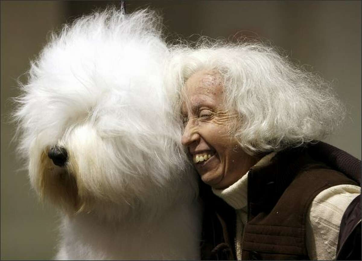 """Charlene Stahl, of Seattle, snuggles up to """"Crystal Blue Ice,"""" an Old English sheepdog owned by Colleen Grady and Dea Freiheit. """"We're twins, we even have the same blue eyes,"""" Stahl said."""