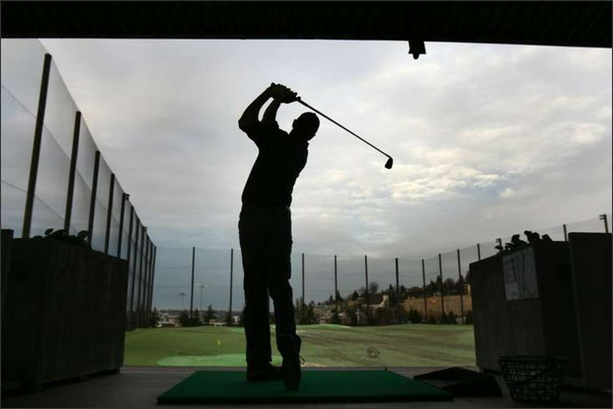Austin Wood, of Tukwila, a regular at the Interbay Golf Center's driving range, practices his swing at the neighborhood landmark recently. After Interbay's few shops, close, everyone leaves.