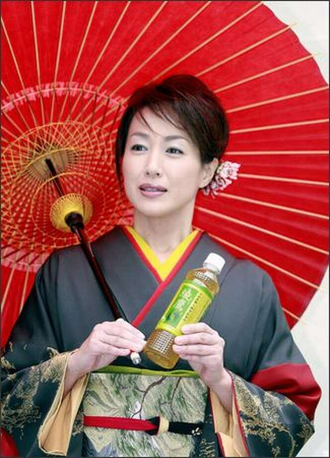 Japanese actress Reiko Takashima holds a bottle of Japanese green tea for a promotional shoot. Green tea is credited with regulating cholesterol and burning fat, and can be calming, too. Photo: / Getty Images