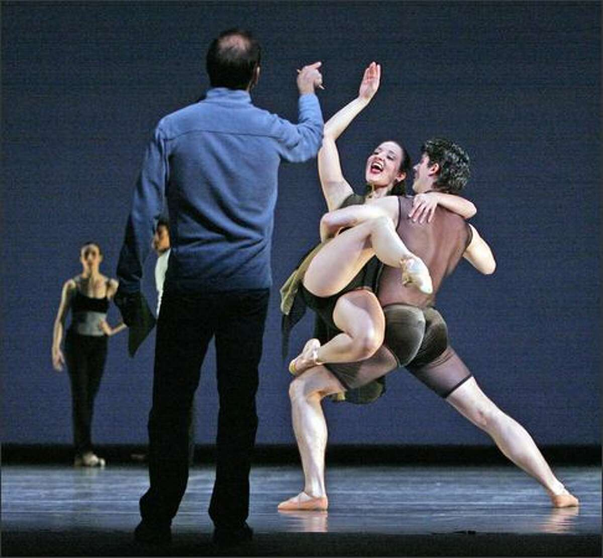 Sense of Doubt's choreographer Paul Gibson, with back to camera, laughs with a dancer after they get a dance move done correctly at the end of the rehersal. PNB dancers perform Paul Gibson's Sense of Doubt in the Pacific Northwest Ballet DIRECTOR'S CHOICE presentation at McCaw Hall. DIRECTOR'S CHOICE performances run March 13-22, 2008.