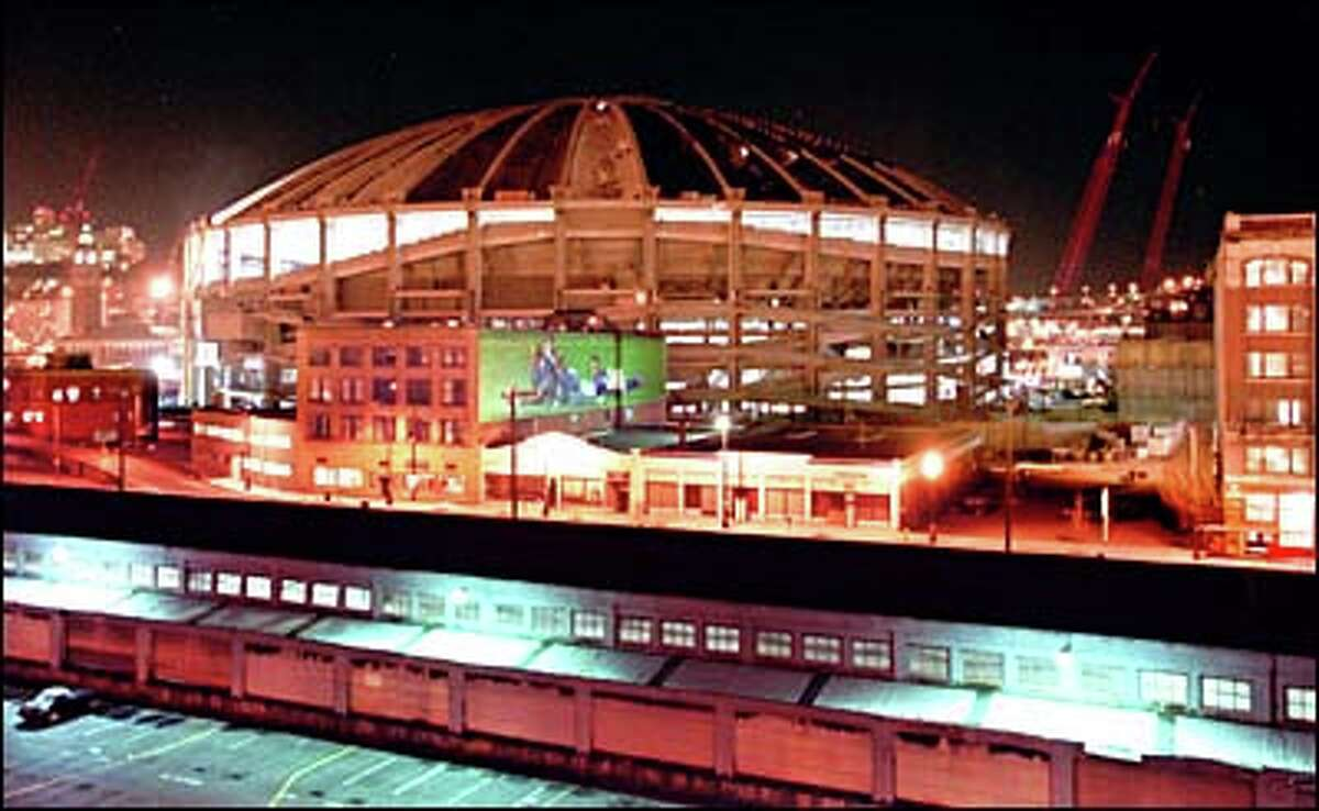 With its walls partially torn away, interior lights turn the Kingdome into a glowing beacon after dark.