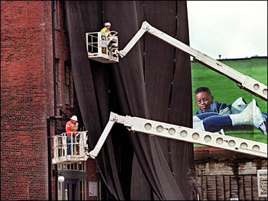 Workers from TLH Abatement work on placing Geo cloth, a feltlike material, to protect buildings along Occidental Avenue from dust and shrapnel during the implosion of the Kingdome on Sunday. Photo: Renee C. Byer, Seattle Post-Intelligencer