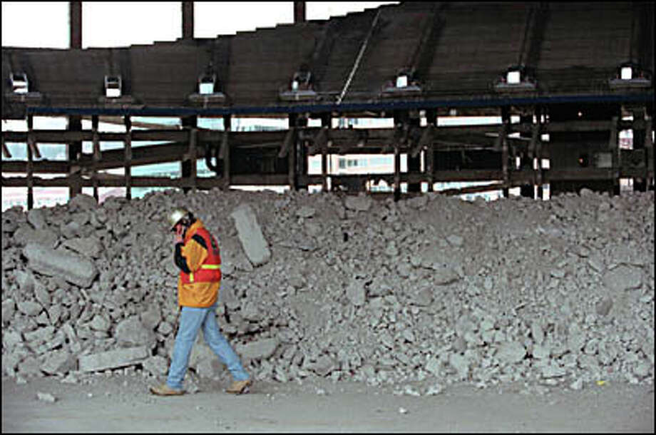 Rick Riggs, operations manager for Aman Environmental Construction of Covina, Calif., talks on his cell phone amidst the remains of the Dome.  His company is responsible for tearing down the bulk of the Kingdome. Photo: Renee C. Byer, Seattle Post-Intelligencer