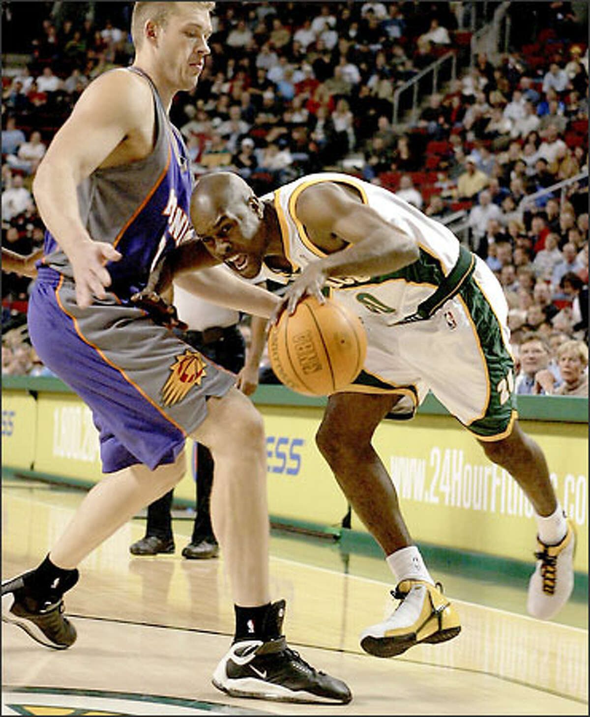 Sonics point guard Gary Payton drives around the Suns' Jake Tsaklidis last night at KeyArena. Payton scored 20 points, and his three-pointer with 1:19 left clinched the victory after Phoenix had cut the lead to six points.