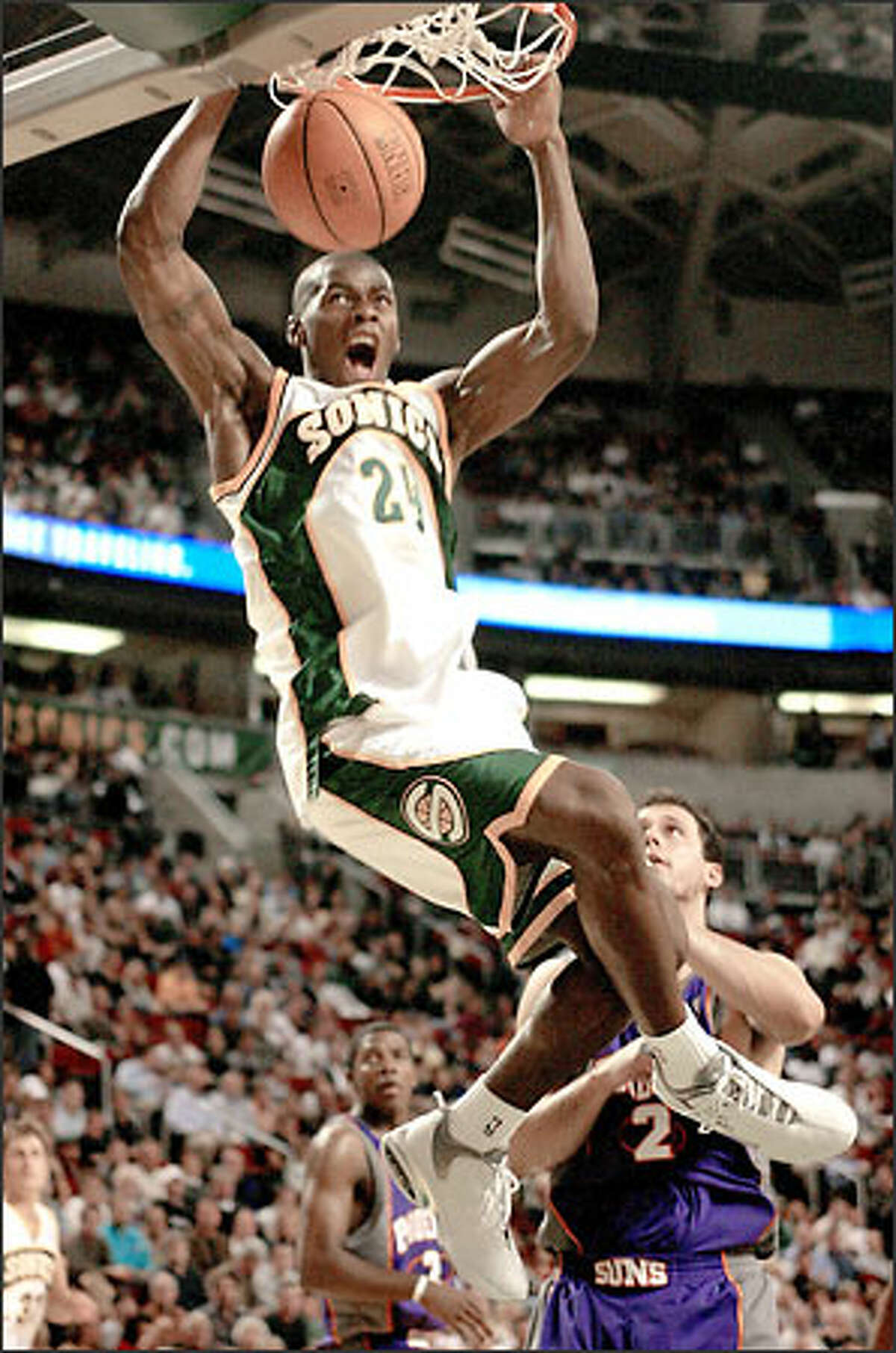 Desmond Mason gets off a powerful slam-dunk over the Phoenix Suns' Joe Johnson early in the Sonics' 86-73 win last night.