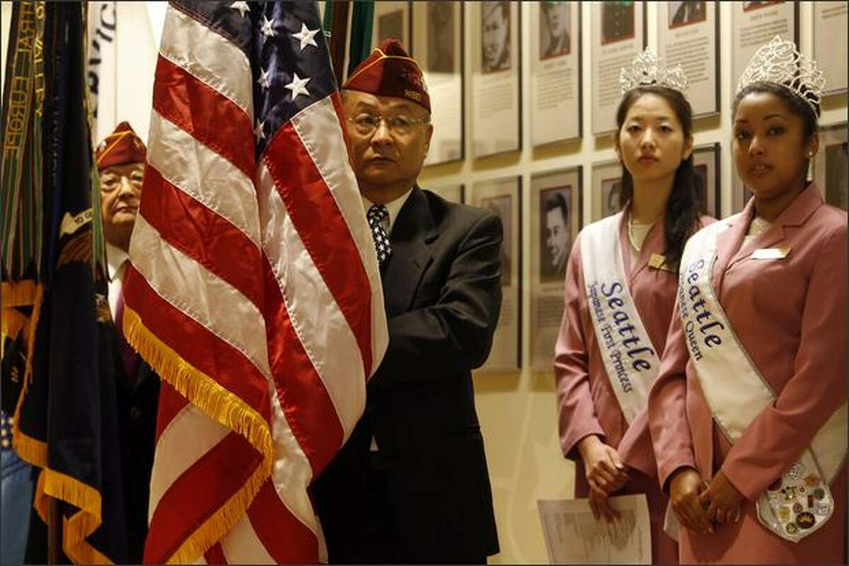 Nisei Veterans Committe Honor Guard members Teruo Yorita, center left, and Tom Ohtani, left, wait in the wings along with Seattle Japanese Queen Monique Aiyaka Perkins, right, and First Princess Lisa Felice Akiyama, center right, for the start of the ceremony dedicating the newly renovated Nisei Veterans Committee Memorial Hall in Seattle on Saturday.