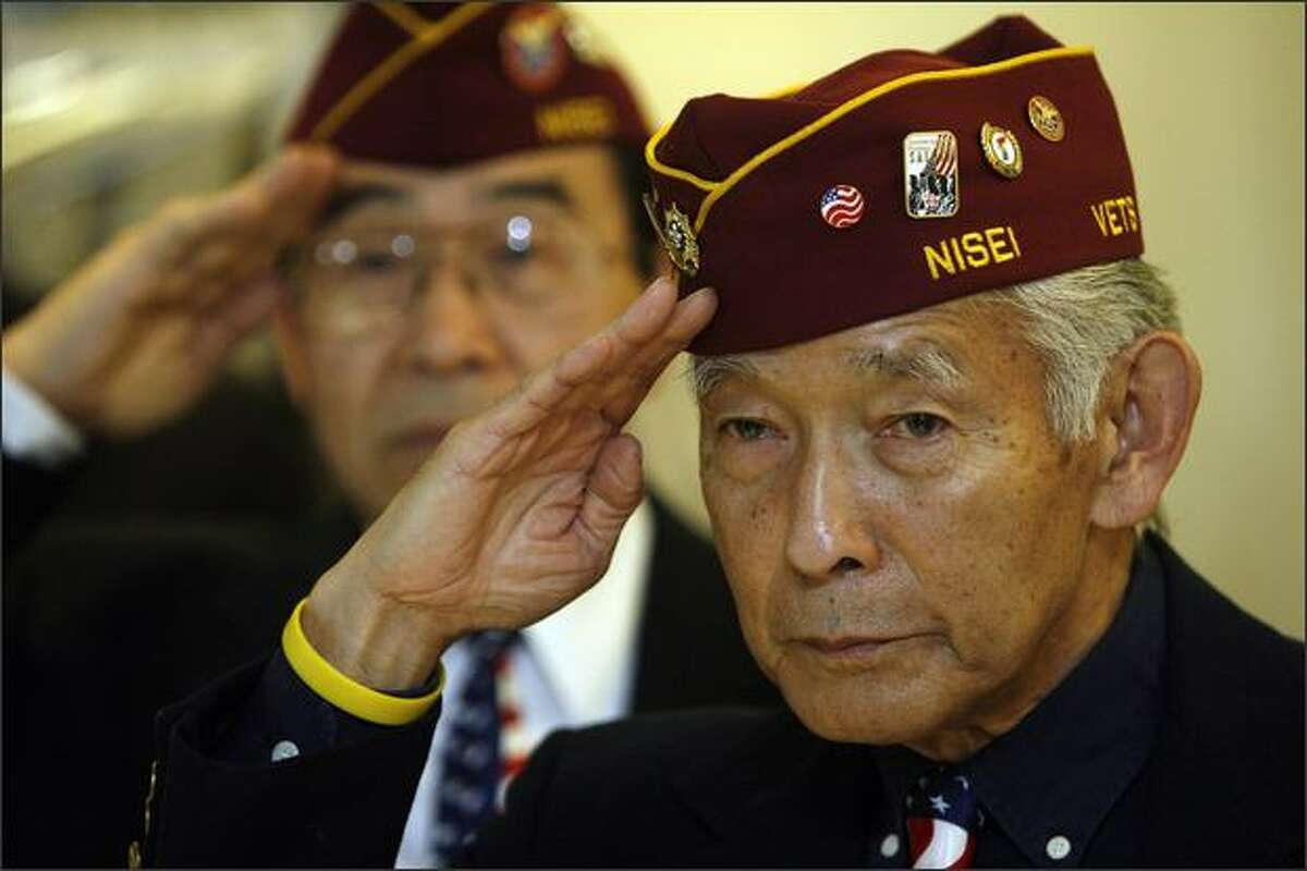 Nisei veterans Sam Mitsui, right, and Dale Kaku, left, salute during the national anthem at ceremonies dedicating the newly renovated Nisei Veterans Committee Memorial Hall in Seattle on Saturday.