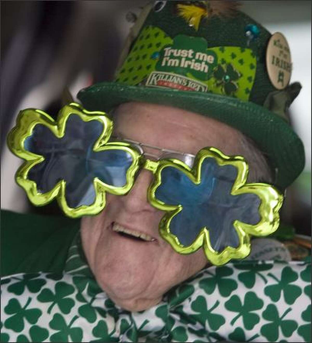 Harvey Losh, 90, enjoys the 37th annual St. Patrick's Day Parade while riding in the back of an SUV in Seattle.