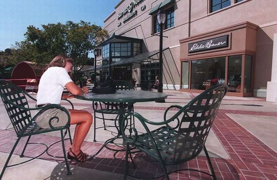Those green metal chairs have been at University Village for a long time. This 1995 photo shows Amy Sherbrook filling out a job application for the Gap while sitting in the then newly remodeled plaza of University Village. (Grant Haller/seattlepi.com file) Photo: P-I File