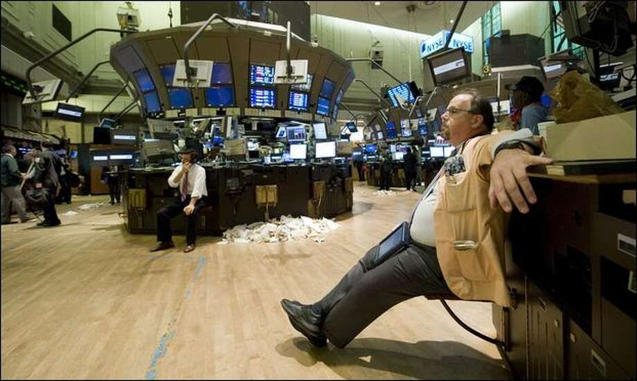 At the New York Stock Exchange, trader Michael Kilkenny reflects on the collapse of the markets Monday. The Dow closed at its lowest level in nearly three years. Photo: Richard Drew/Associated Press