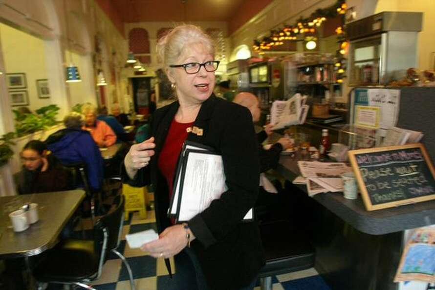 Mom's cafe owner Denise Breen helps customers at Mom's in the University Village, Jan. 2003. One of