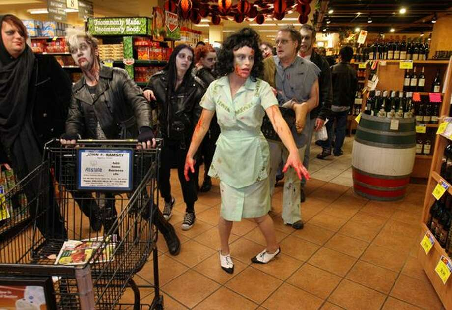 Wendy Watkins of Seattle, pushing shopping cart, and Gelsey Hanson, also of Seattle, and fellow Zombies invade QFC at University Village during their Zombie Walk on Oct. 29, 2006. About 150 un-dead participated in an hour-long walk. Photo: P-I File