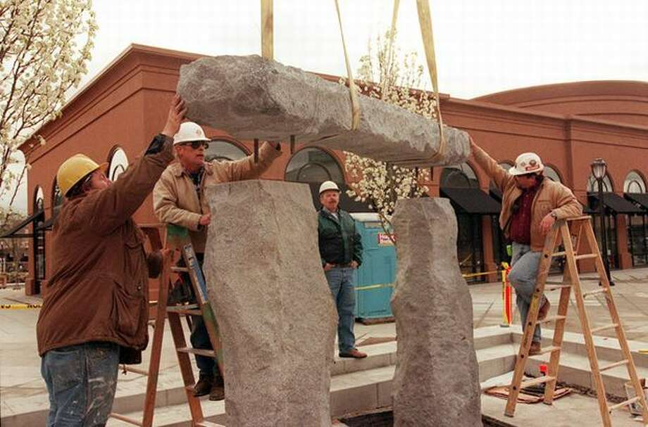 """The March 1998 caption of this photo read: """"Workers place one of the top pieces of cascade granite in place at the new fountain in the Northwest Quadrant at University Village. The Plaza Fountain was designed by local landscape architect Tom Berger."""" Photo: P-I File"""
