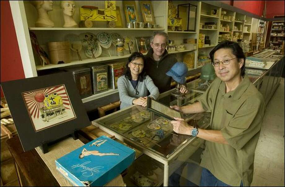 Binko Chiong-Bisbee and John Bisbee, owners of Kobo at Higo, left, and Paul Murakami stand at a counter that was in the original store at Sixth Avenue South . and South Jackson Street. The whole area is full of artifacts on display from the old store. Photo: Grant M. Haller/Seattle Post-Intelligencer