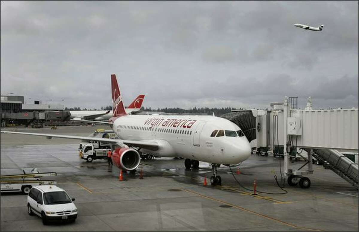 The first Virgin America flight from San Francisco sits at gate A6 after arriving at Seatac International Airport. An Alaska Airlines flight takes off nearby.