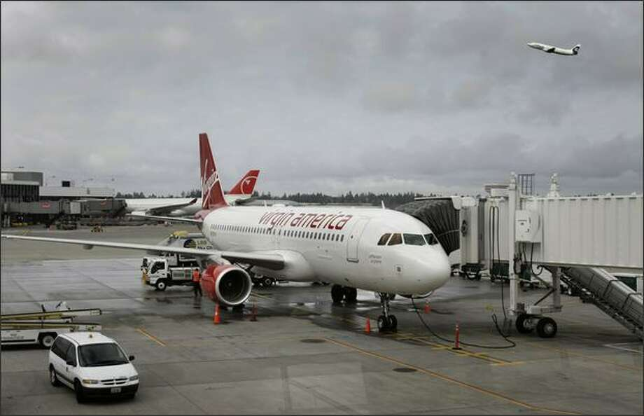 The first Virgin America flight from San Francisco sits at gate A6 after arriving at Seatac International Airport. An Alaska Airlines flight takes off nearby. Photo: Andy Rogers, Seattle Post-Intelligencer