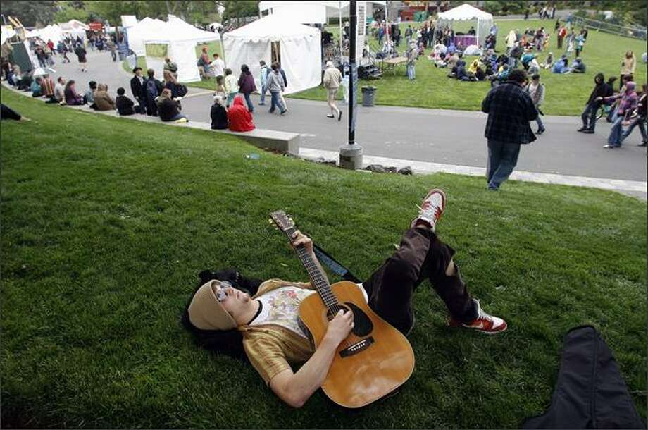 Brennan Moring of Redmond strums his guitar while relaxing at the Folklife Festival at Seattle Center in May. Photo: Mike Urban/Seattle Post-Intelligencer