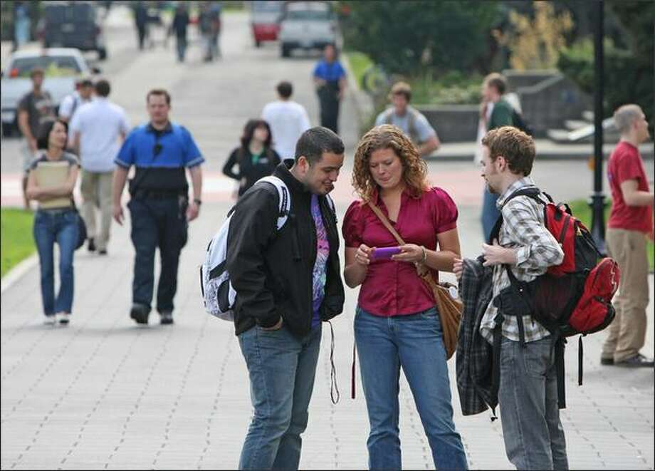 """From left, Seattle University student Adam Trevino talks with Lexi Fish and Brett Horvath about """"Your Revolution,"""" as Fish and Horvath work to register young voters. Photo: Mike Kane/Seattle Post-Intelligencer"""