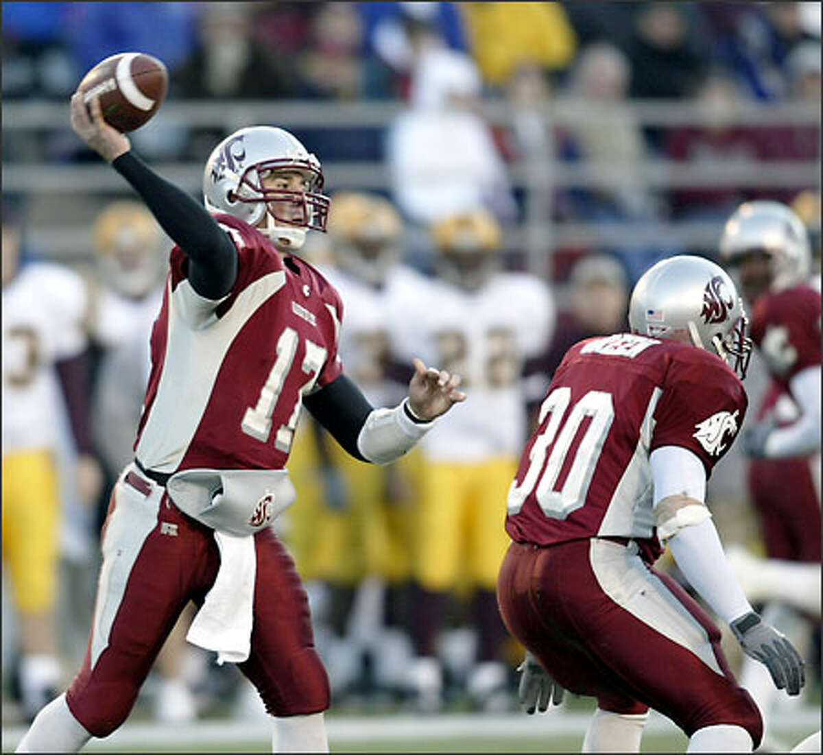 Washington State quarterback Jason Gesser, left, passes in the fourth quarter against Arizona State to break the old WSU passing record set by Jack Thompson in 1978, Saturday, Nov. 2, 2002, at Martin Stadium in Pullman, Wash. Running back Jermaine Green, right, protects Gesser on the play. (AP Photo/Jeff T. Green)