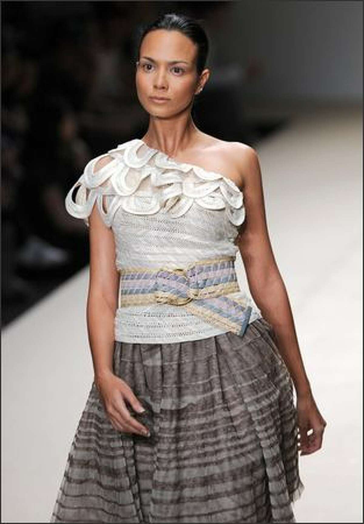 A model walks the runway wearing outfits of Kai by Thai designer Somchai Kawtong.