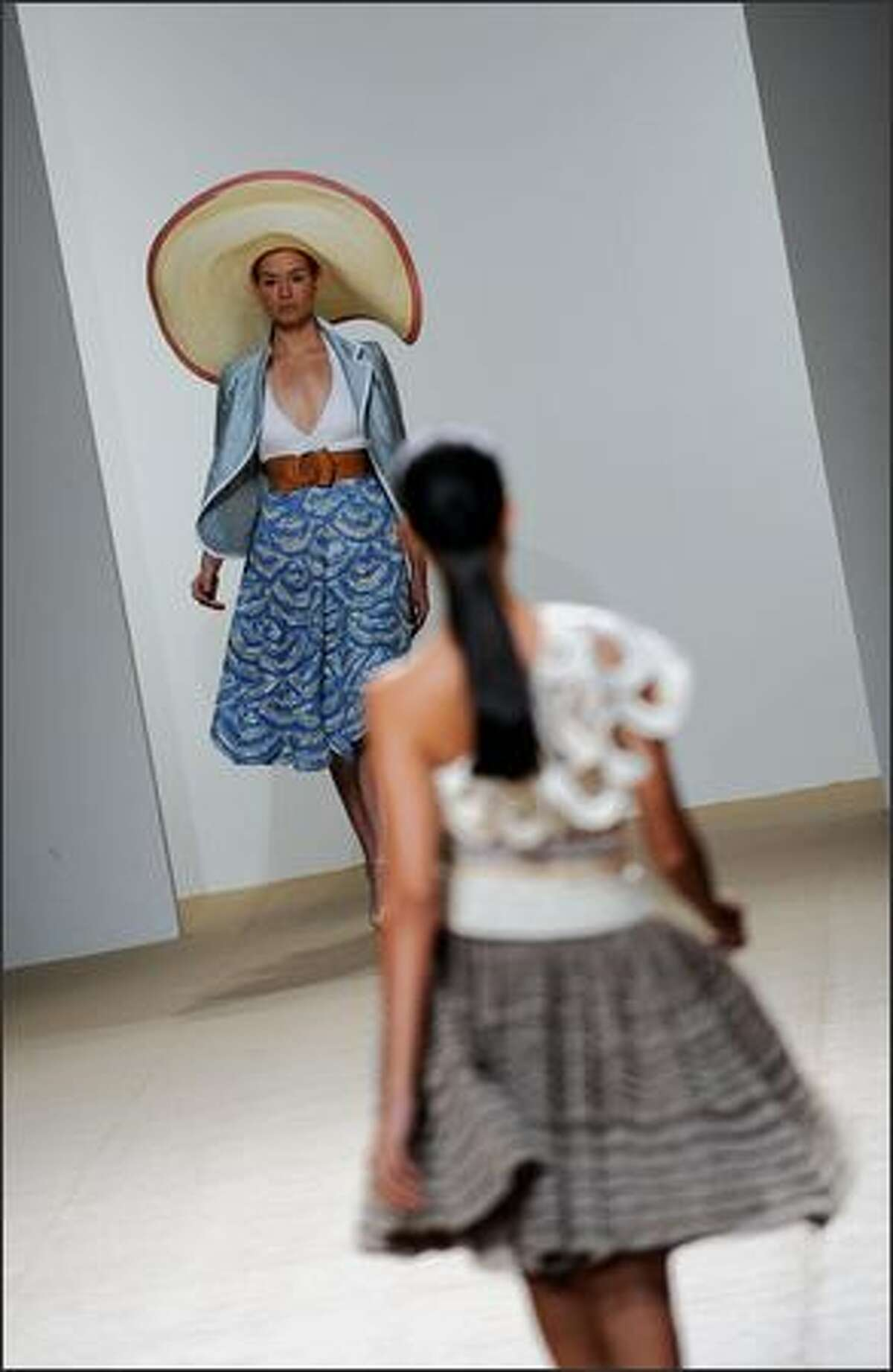 Models display outfits of